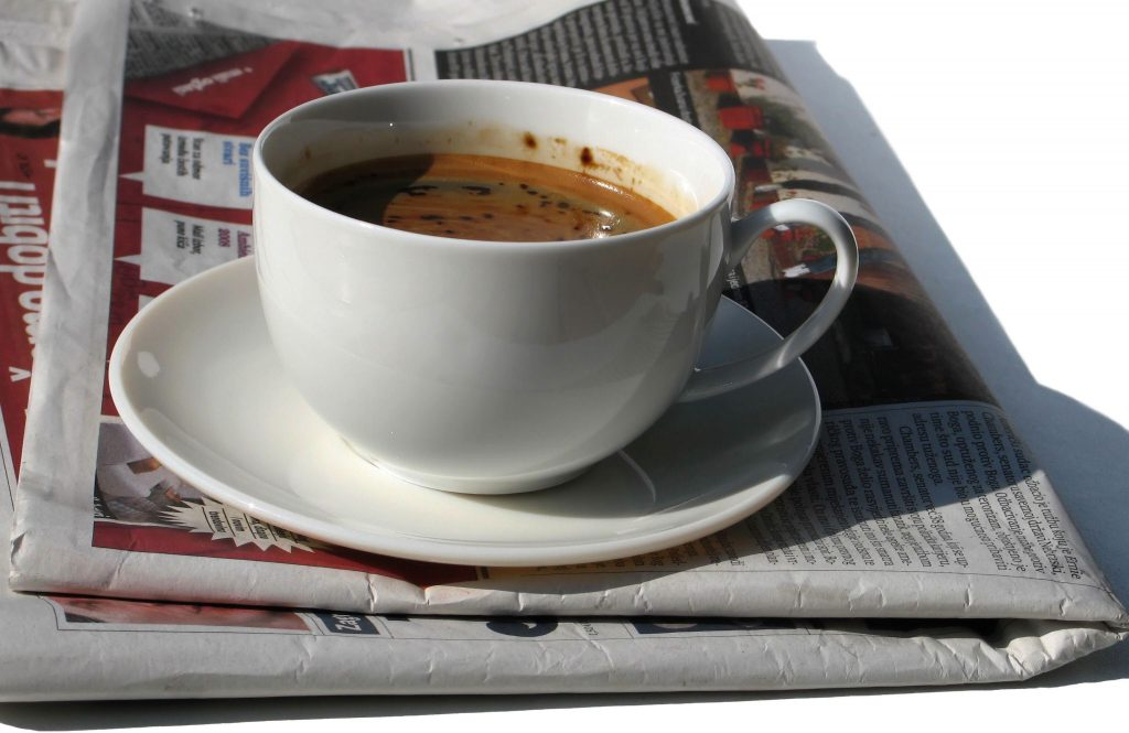 Cup of coffee and a newspaper.